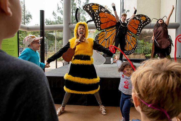 Adultos vestidos de abelha, borboleta e barata fazem uma peça para as crianças na Bug Fair. ...