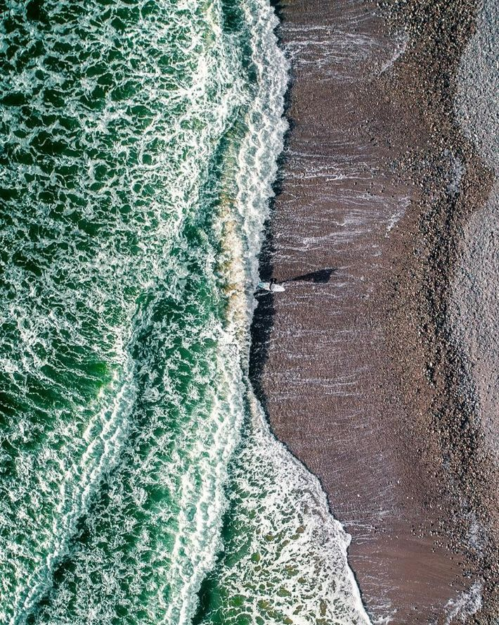 Surfista emerge do mar gelado da Irlanda, perto da cidade costeira de Tramore.