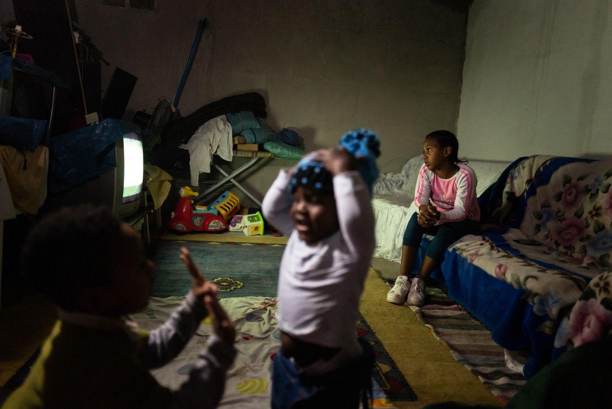 Tiago, um ano, e Clemente, cinco, brincam na sala, enquanto atrás Analese, de nove, vê televisão. ...