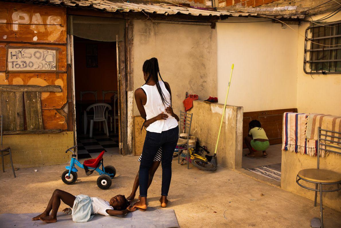 Edna Nazaré, 37 anos, dança à porta de sua casa com uma das filhas. Para Edna, o ...