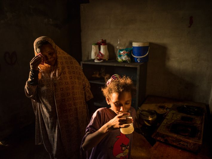 Um Khaldoun seca o suor do rosto enquanto sua filha bebe água no calor implacável do ...