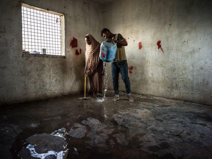 Um Khaldoun limpa o chão de casa com seu filho em um dia muito quente. A ...