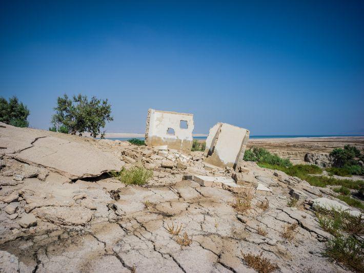 Construção se esvai em um solo colapsado, engolida pela erosão decorrente do encolhimento do Mar Morto, ...
