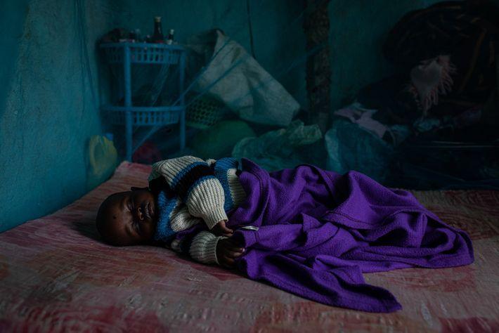 Prince Jackson, com dez meses de idade, dorme sob uma rede mosqueteira em sua casa no ...