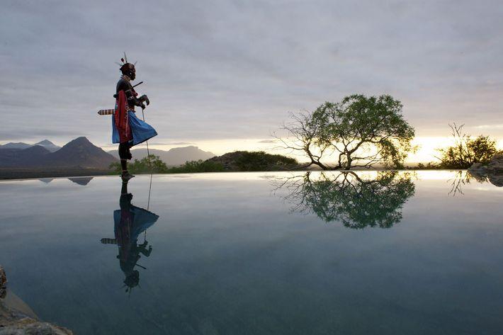 Um guerreiro Samburu observa uma piscina no Sarara Camp, que é inteiramente de propriedade e administrada ...
