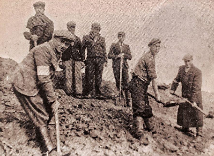 Kiwa (segundo a partir da direita) com amigos em mutirão de trabalho em Słupia, Polônia, em ...