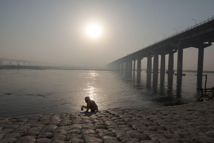 Um sadhu, ou homem sagrado, recolhe água do rio Ganges durante o Kumbh.