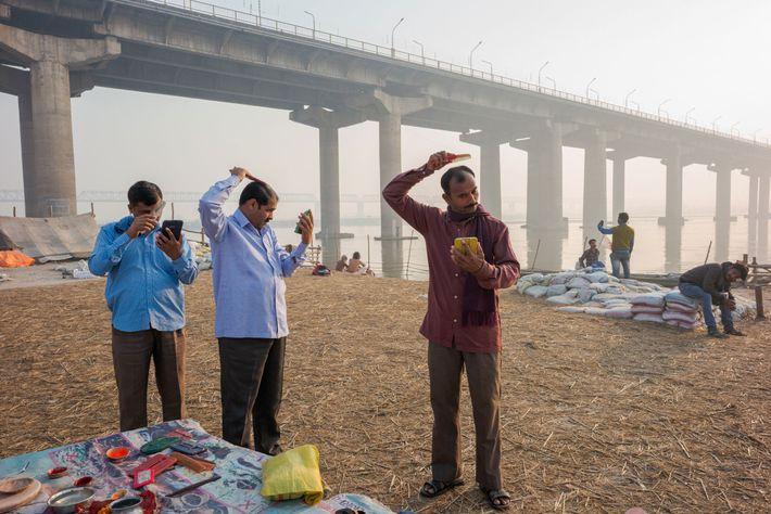 Peregrinos hindus às margens do rio Ganges se preparam para um dia no Kumbh.