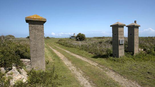 Os portões de entrada do campo de concentração nazista Sylt estão entre as poucas ruínas visíveis ...
