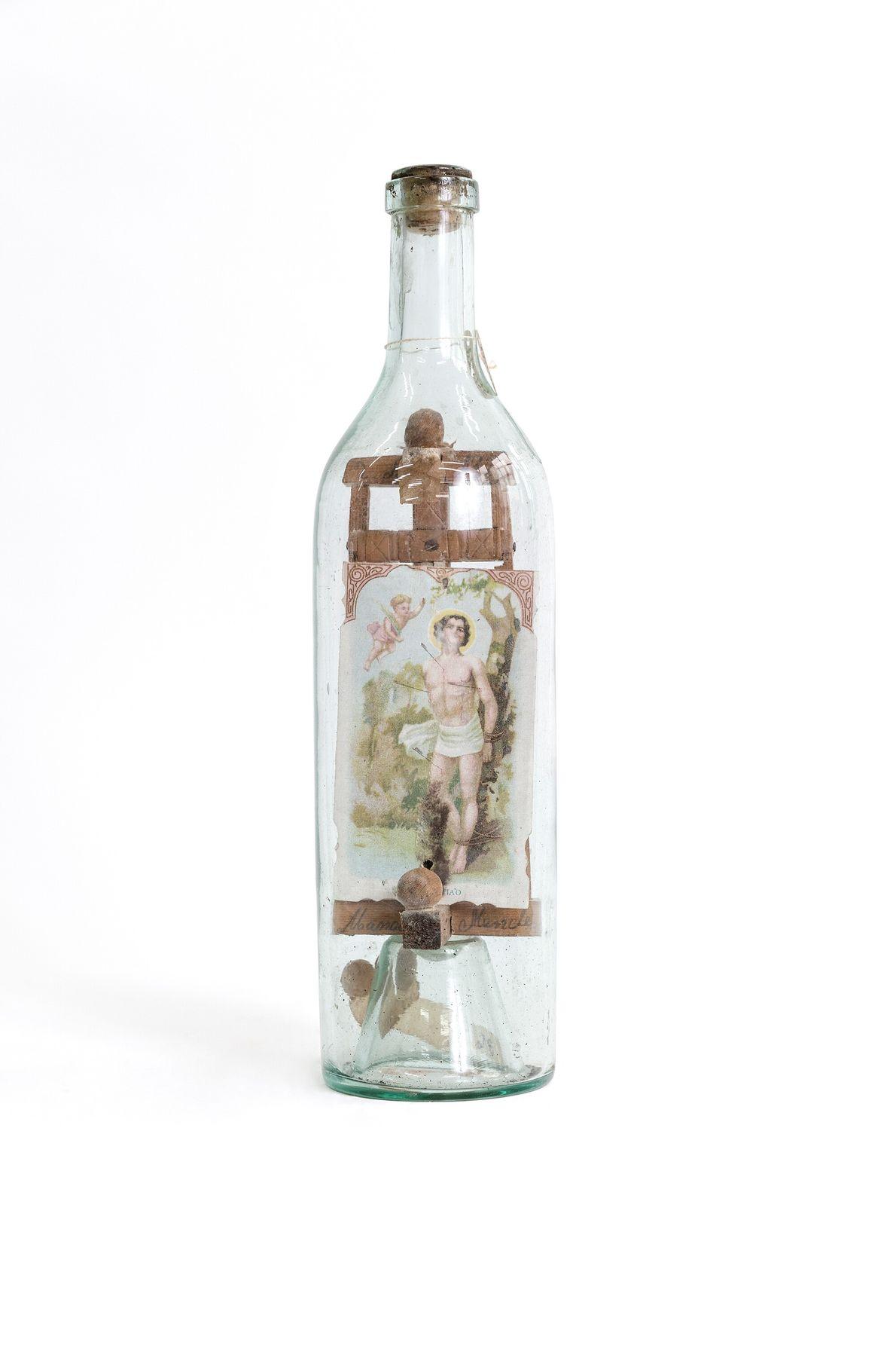 Garrafa contendo uma pequena estrutura em madeira e imagem de São Sebastião, santo comumente associado a ...