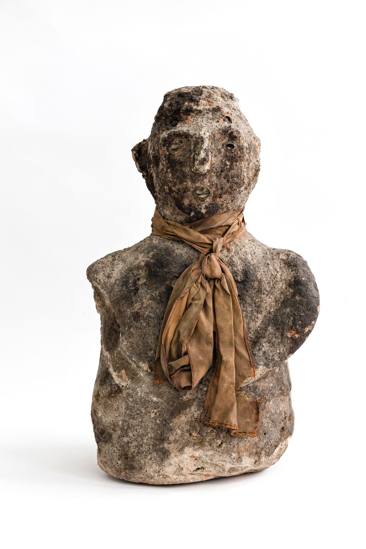 Figura humana com cabeça, tronco e braço esquerdo junto ao corpo, e búzios incrustrados nos olhos, ...