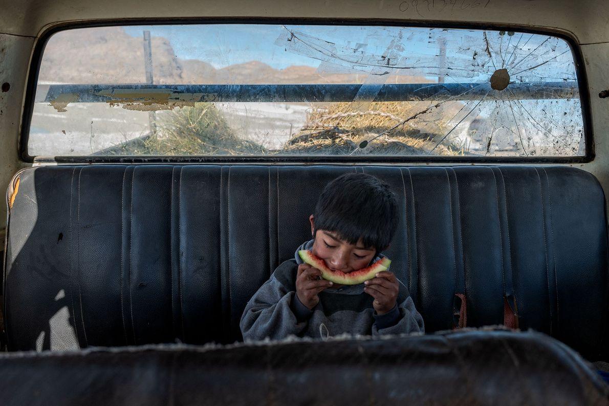 Angelo Martín Flores Chambi faz uma pausa para um lanche na picape Chevrolet de sua família, ...