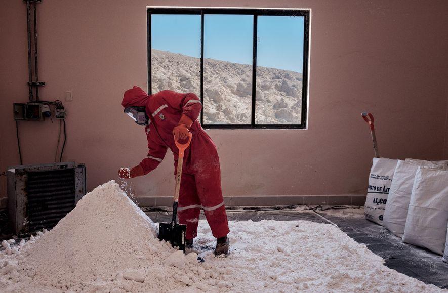 Um trabalhador verifica se o carbonato de lítio está seco, na etapa final antes de o ...