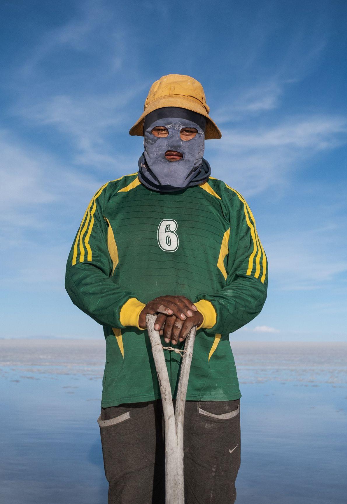 Wilmer Flores, com o rosto coberto para se proteger do sol, recolhe sal perto do Salar ...