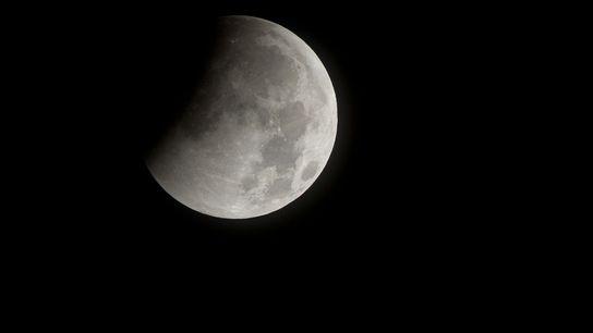 A sombra da Terra escurece a lua no início de um eclipse lunar total em dezembro ...