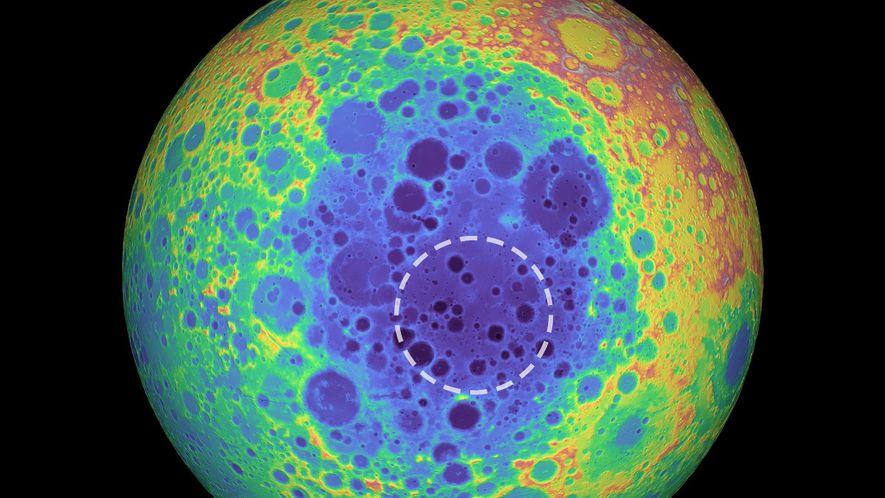 Esta imagem de cores falsas demonstra a topografia no lado oculto da Lua, sendo as partes mais altas representadas por cores quentes e as mais baixas por cores frias. Um círculo pontilhado indica a zona com excesso de massa sob a bacia do Polo Sul-Aitken.