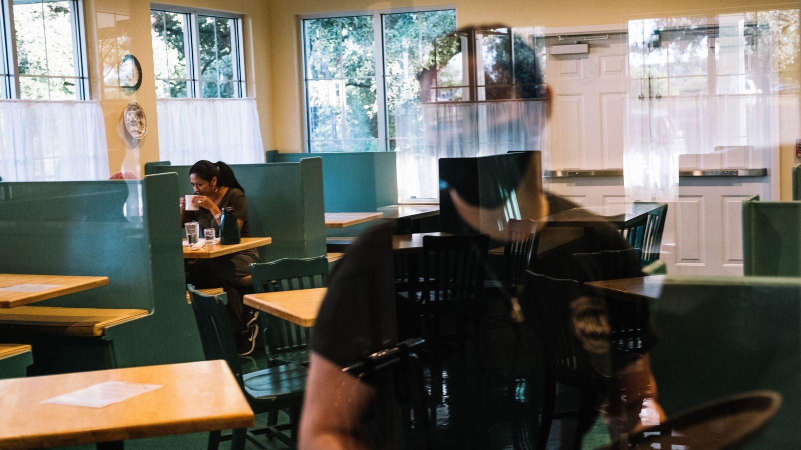 Uma cliente em sua mesa e um garçom no Magnolia Pancake Haus, em San Antonio, Texas, ...