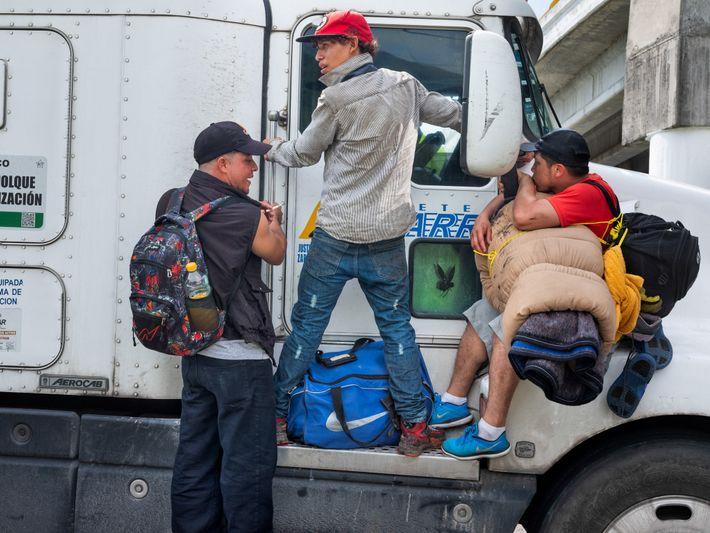 Migrantes da América Central, parte de uma caravana de milhares, pegam carona na traseira de um ...