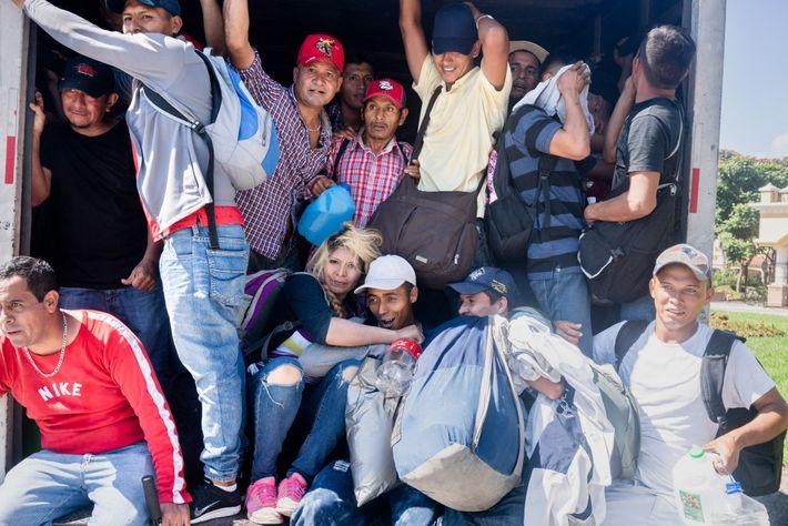 Migrantes salvadorenhos amontoam-se dentro do baú de um caminhão que os ofereceu carona em direção à ...
