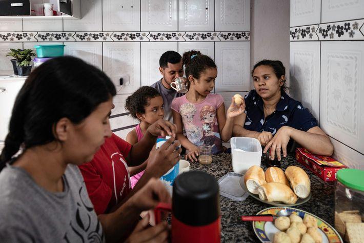 Uma família se aglomera na cozinha para tomar café da manhã. Os cômodos estreitos na favela ...