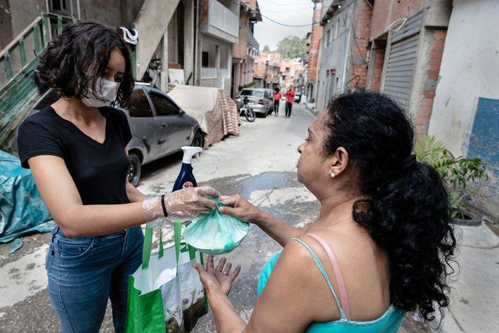 Maria Angelica de Araújo Costa entrega refeições depois de desinfetar as mãos de uma moradora. Água limpa ...
