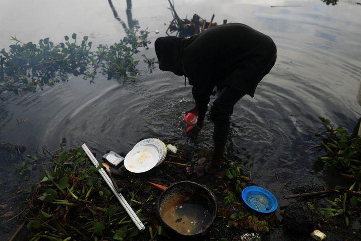 Um pescador lava pratos no lago Naivasha após um almoço com peixes recém-pescados.