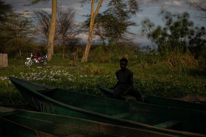Um homem sentado em um barco de pesca na Praia da Tarambeta. Atrás dele, a vegetação ...