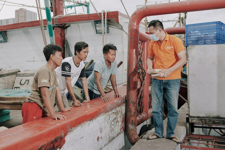Pescadores e trabalhadores no porto de Muara Angke, uma área densamente povoada no norte de Jacarta, ...