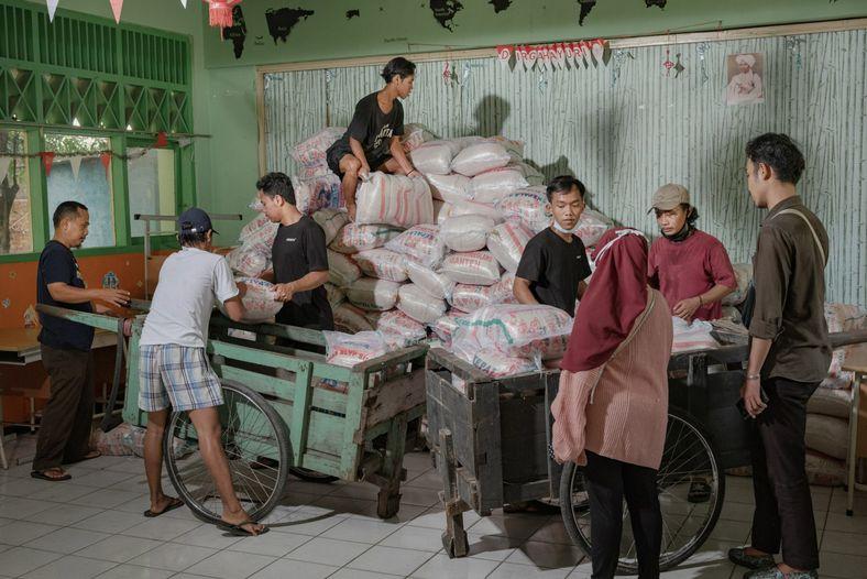 Voluntários da Foodbank of Indonesia descarregam e armazenam 20 toneladas de sacos de arroz na sala ...