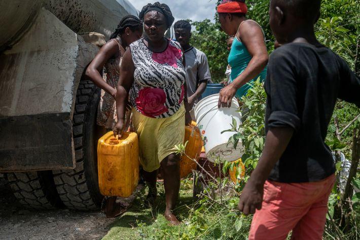 Mulher afasta galões de vizinhos também desesperados por sua quota de água. Após o terremoto, o ...