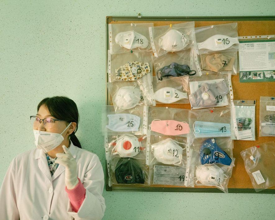 Uma cientista no Green Crown, laboratório independente em Ulaanbaatar, parada do lado de máscaras faciais que ...