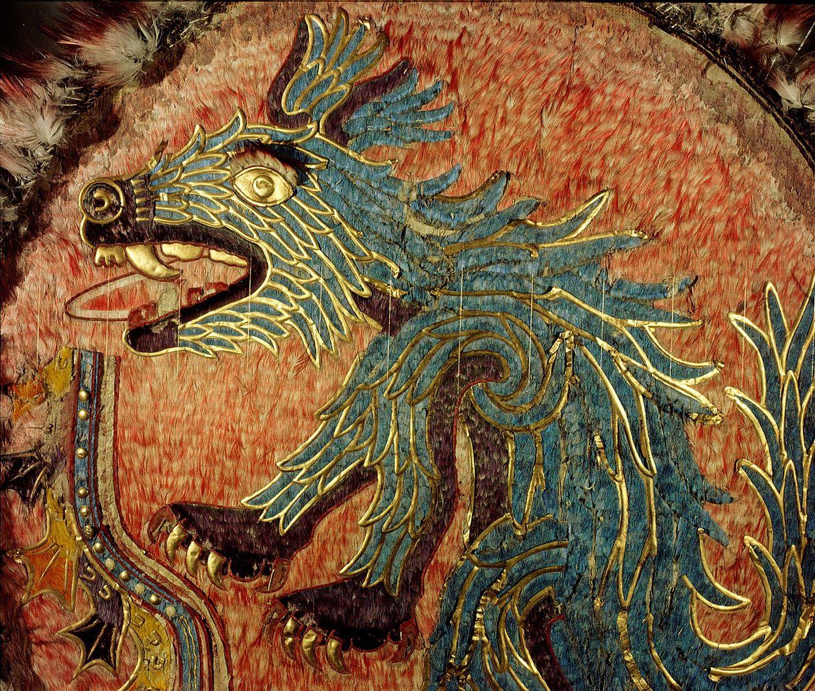 A criatura azul com uma faca na boca, que adorna esse escudo cerimonial feito de penas, ...