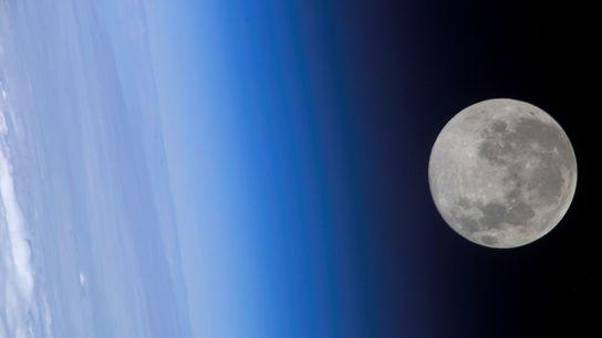A lua cheia parece encostar na atmosfera terrestre, visto da Estação Espacial Internacional.
