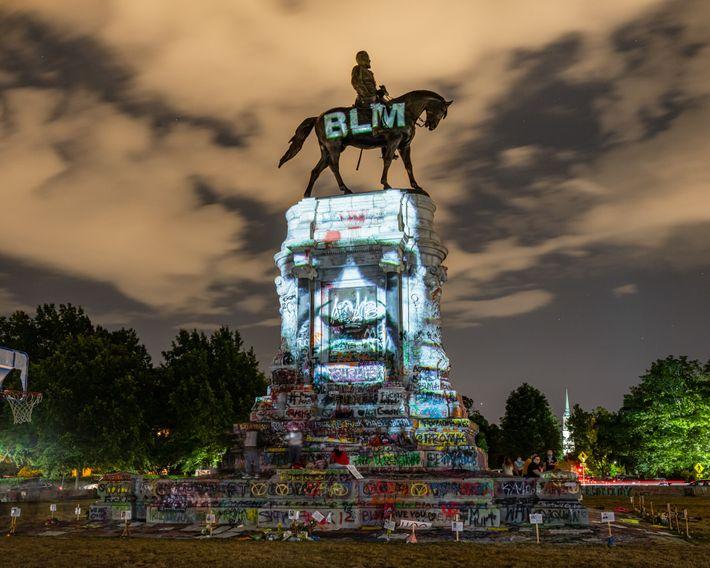 Uma imagem de George Floyd, morto por policiais de Minneapolis, Minnesota, é projetada no monumento pichado ...