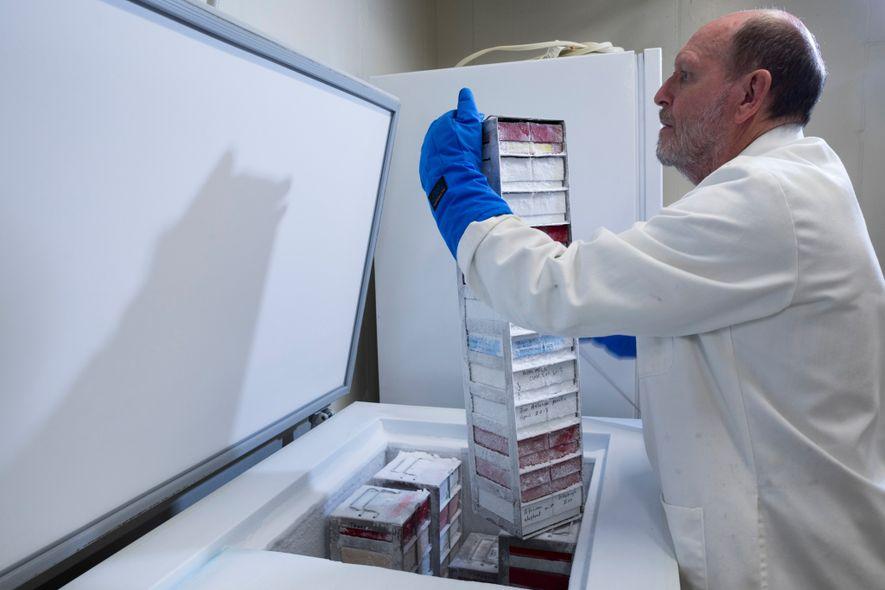O cientista Mike Power, responsável pela curadoria e manutenção do repositório de leite, puxa uma pilha ...