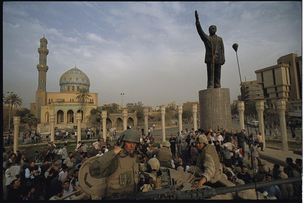 2003  Fuzileiros navais dos Estados Unidos ajudam iraquianos a derrubar uma estátua de Saddam Hussein na Firdos ...
