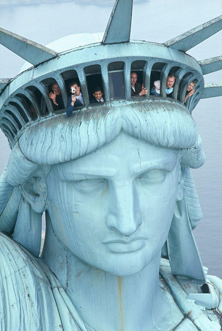 Foto da cabeça da estátua da liberdade com turistas dentro