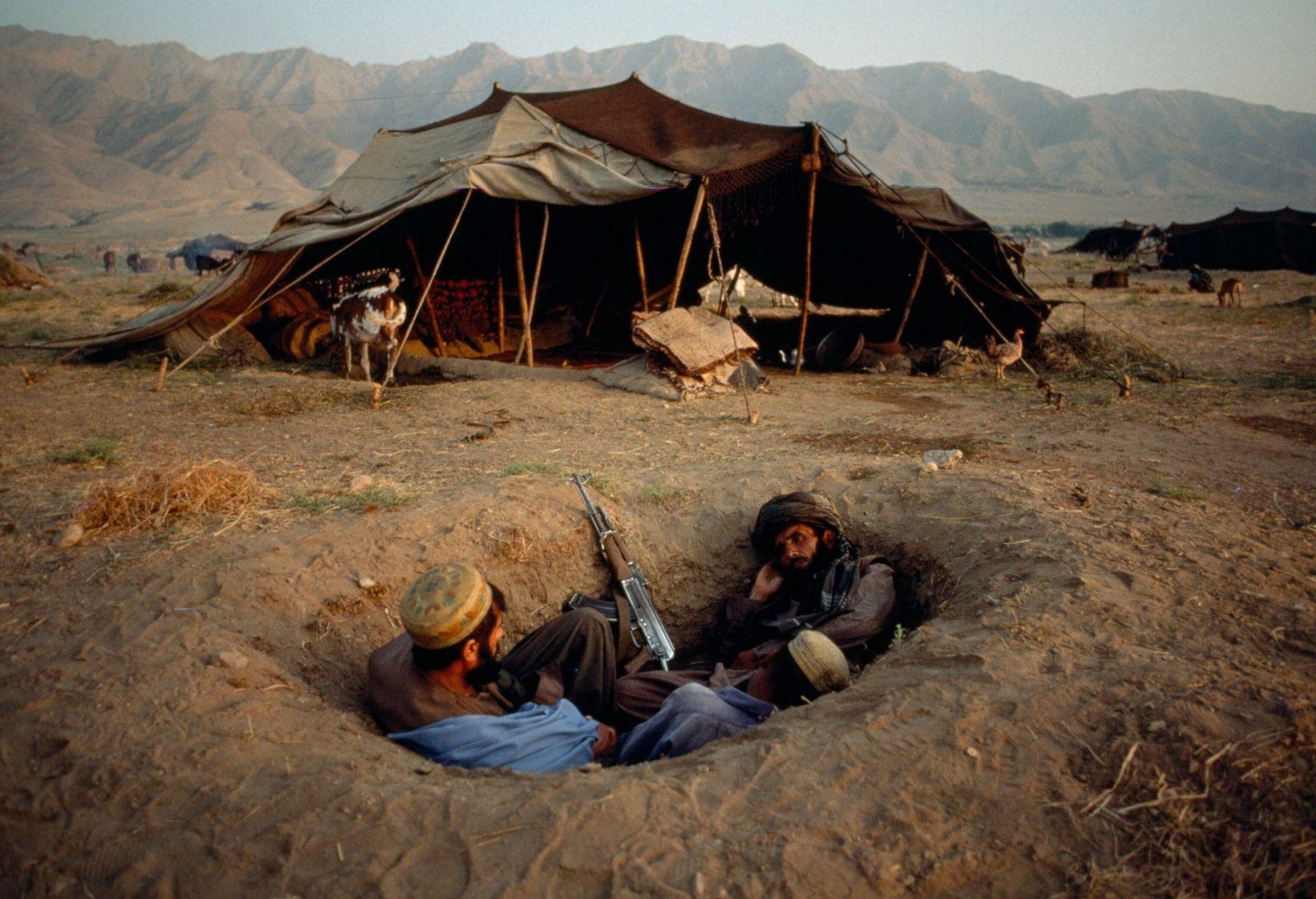 Dois combatentes afegãos buscam cobertura durante o conflito de 2001. Os Estados Unidos invadiram o Afeganistão ...