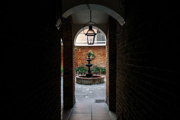 Uma passagem de tijolos leva a um quintal privativo no histórico bairro French Quarter de Nova ...