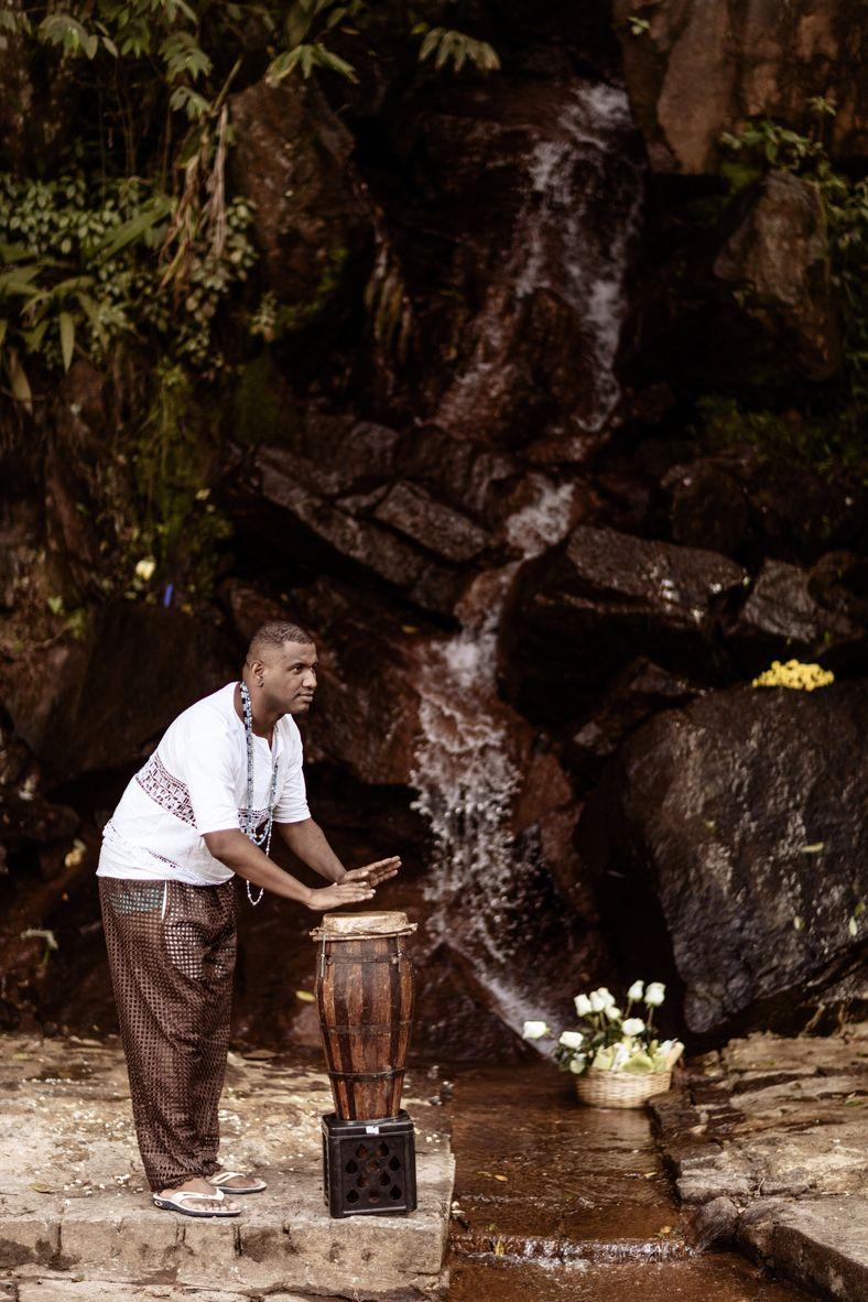O umbandista Denis Cassio da Silva toca atabaque em frente a uma das cachoeiras do Santuário ...