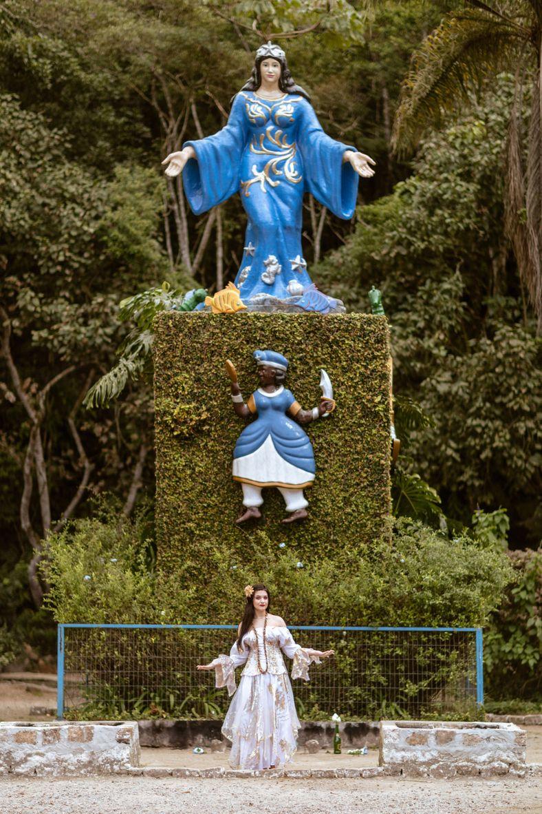 umbandista com vestido branco em frente a estátua em pedestal de oito metros