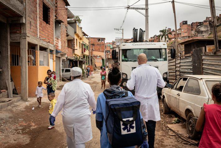 O Dr. Ricardo Vieira da Silva, à direita, caminha com sua equipe para uma consulta domiciliar ...