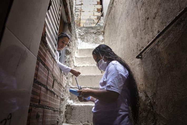 A voluntária da União de Moradores de Paraisópolis, Amanda Barros Vasconcelos Silva, à direita, inscreve uma ...