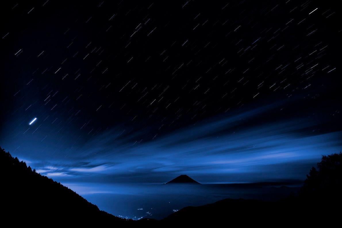 Uma exposição de sete minutos cria trilhas de estrelas acima do Monte Fuji, visto da estrada ...