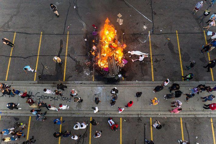 Manifestantes jogam manequins de loja de departamento em uma fogueira no estacionamento em frente à delegacia ...