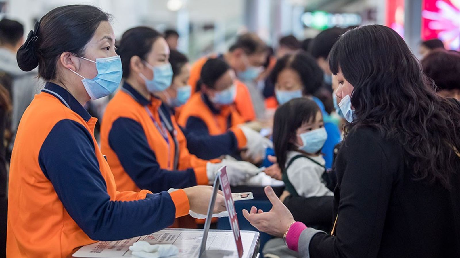 Funcionários ferroviários de Hong Kong, com coletes laranja e máscaras faciais, verificam documentos dos viajantes em ...