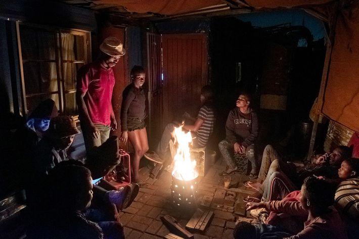 Amigos e familiares sentados na frente de casa em uma noite de sábado para se aquecer ...