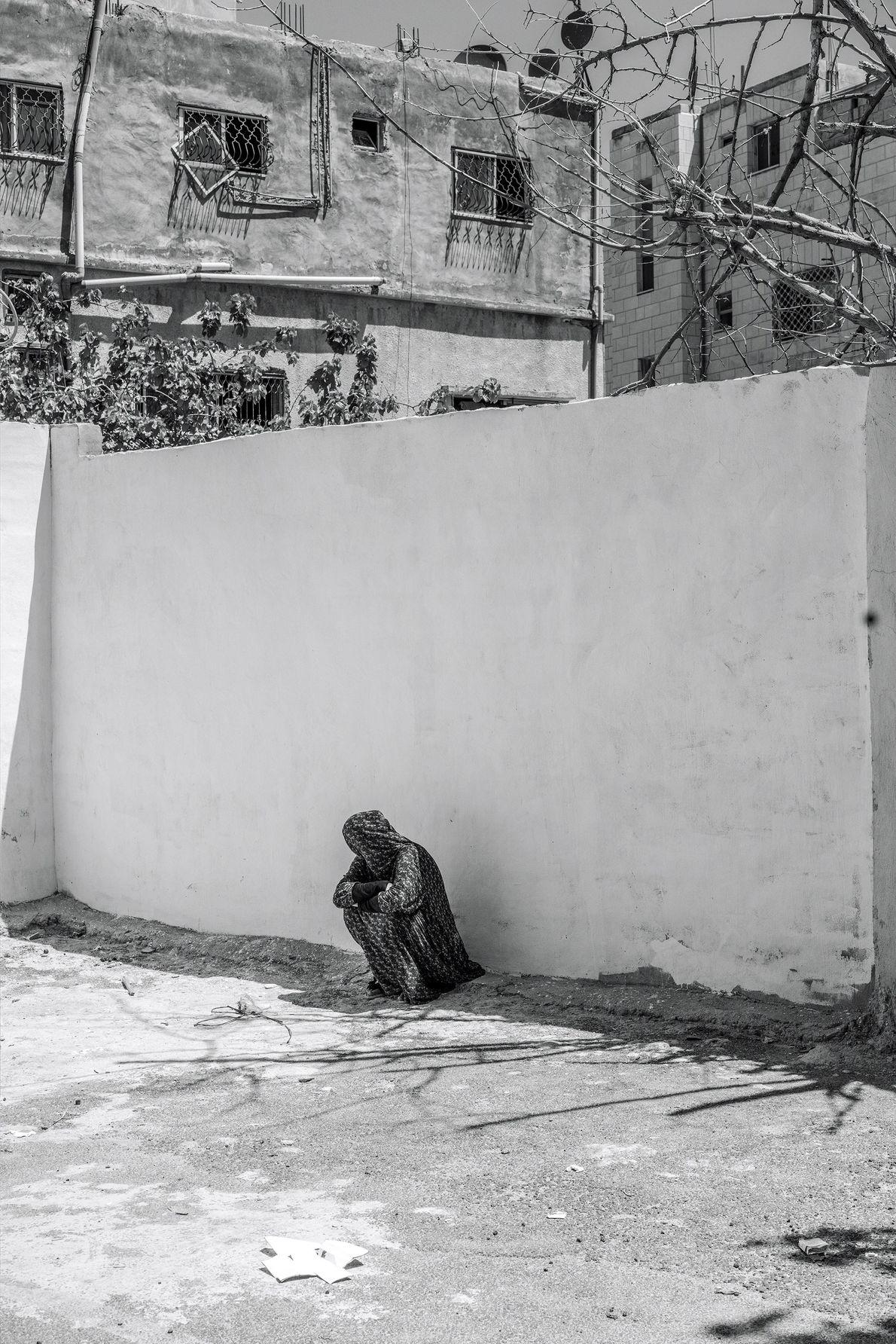 Uma mulher sentada à sombra de um muro no pátio de um centro de acolhida islâmico ...