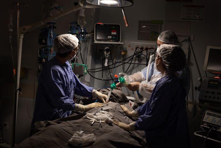 Cirugiões realizam uma traqueostomia em ala de covid-19 do centro de tratamento intensivo do Hospital Geral ...