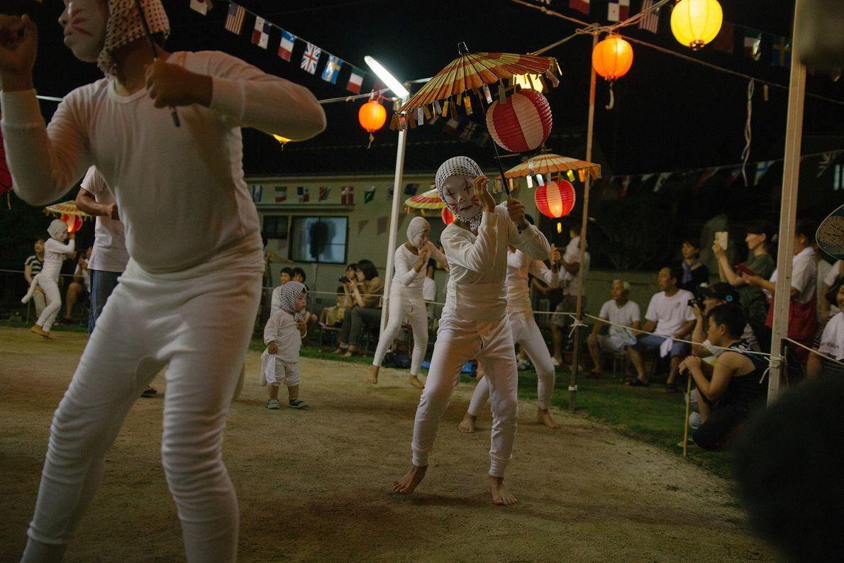 Um grupo de kitsune apresenta a dança Bon ao som de um tambor. As pessoas muitas ...